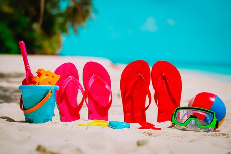 Colored flip-flops, toys and diving mask at beach Stock Photo