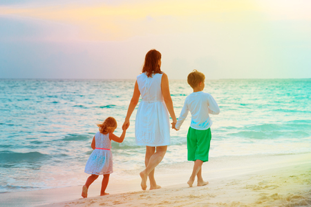 mother and two kids walking on beach 写真素材