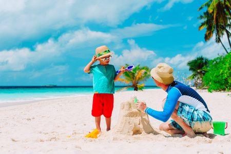 father and son building castle on sand beach Stock Photo