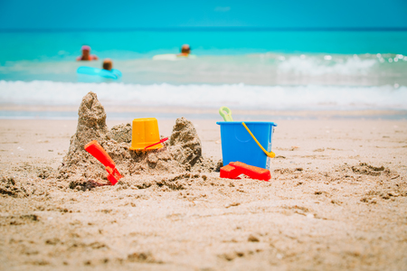 Sand castle on beach and family enjoy tropical vacation