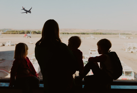 family travel- mother with kids looking at planes in airport