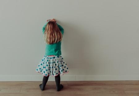 Little girl standing up against a wall Foto de archivo - 96998831