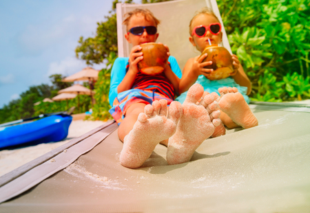 little boy and girl drinking coconut on beach, relax concept Banque d'images