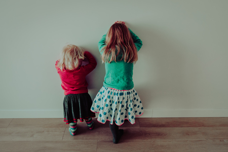 Little girls standing up against a wall