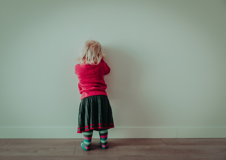 Little girl standing up against a wall