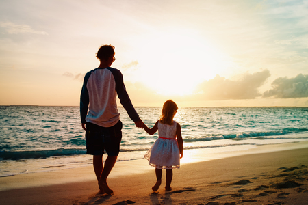 father and daughter walking on beach at sunset