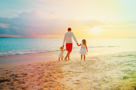 father with two kids walking on beach at sunset