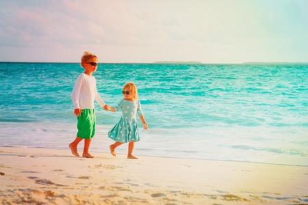 little boy and girl walk on summer beach 写真素材