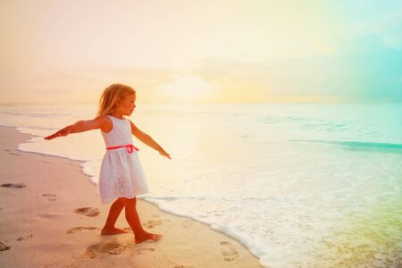 little girl play fly on tropical beach at sunset Stock Photo