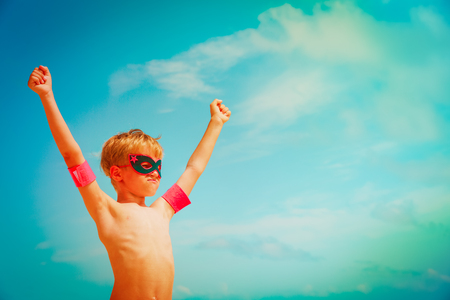 little boy play superhero at sky on beach