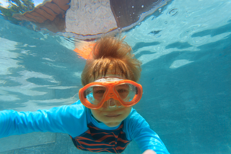 little boy swimming underwater making selfie Stock Photo