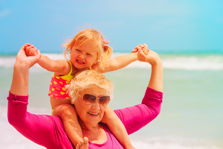 Happy grandmother and little girl play on beach