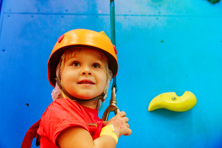 happy cute little girl learn climbing in sport center