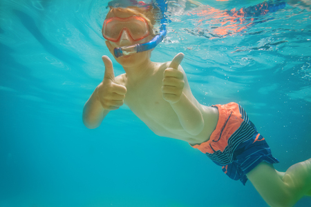happy boy swim underwater with thumbs up