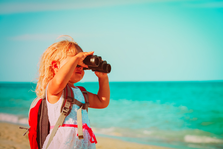 little girl travel on beach, looking through binocular