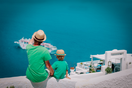 father and little son looking at Santorini, Greece