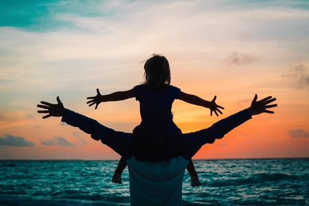 father and little daughter play at sunset sky