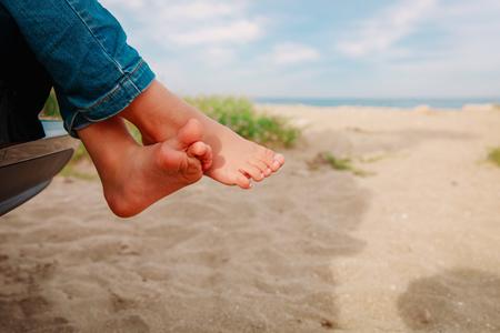 feet of little girl travel by car on beach