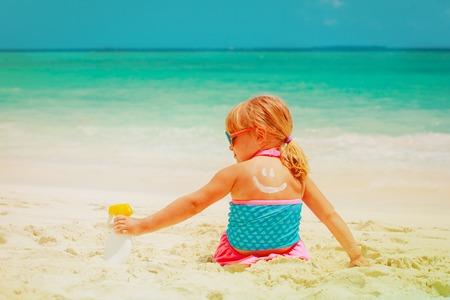 sun protection - little girl applying sunblock cream on shoulder