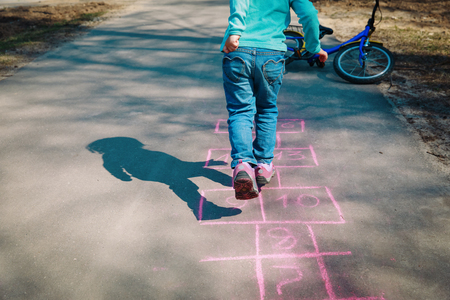 little girl play hopscotch on playground Banco de Imagens