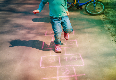 little girl play hopscotch on playground Stock Photo