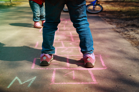 little girl play hopscotch on playground Stockfoto