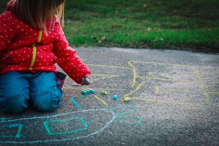 little girl drawing with chalks on playground