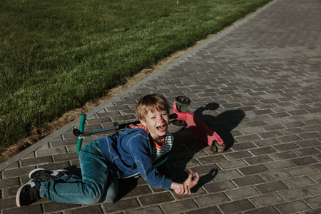 crying child fall off scooter, blood on his face