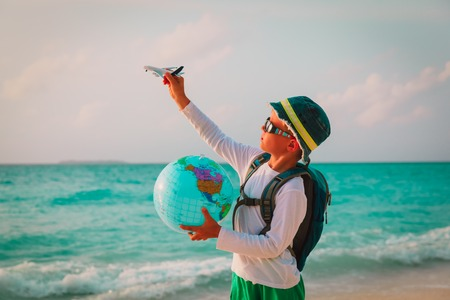 little boy with globe and toy plane travel on beach