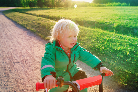little girl learn to ride first bike in nature Stock Photo