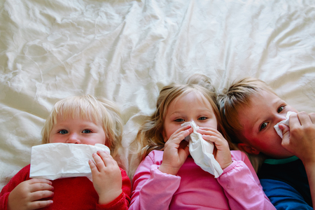 kids wiping and blowing nose Stock Photo
