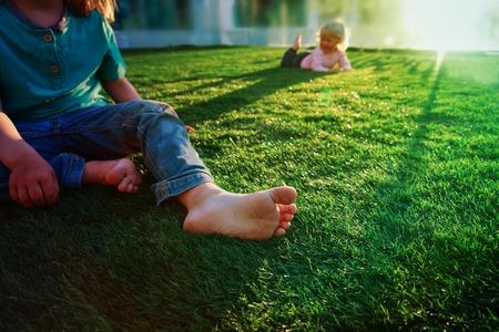 Verano en la ciudad- los niños juegan con los pies sobre el césped en el fondo urbano