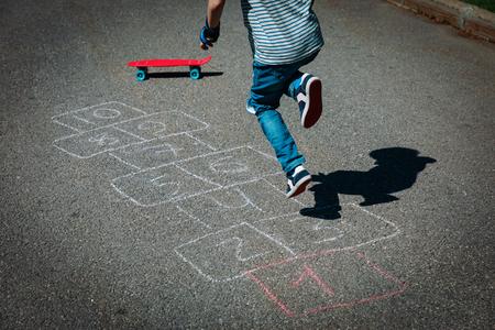 kleine jongen hinkelen op speelplaats