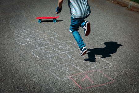 little boy playing hopscotch on playground Stock Photo