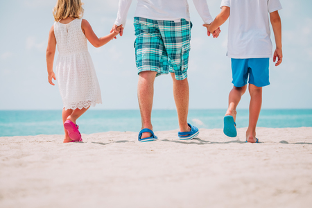 father with son and daughter walking at beach