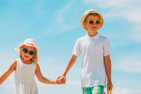 kids- boy and girl walk on summer beach