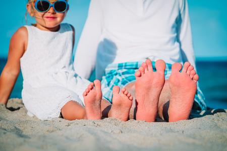 Close up of father and little daughter feet on beach