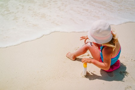 sun protection - little girl with suncream at tropical beach Reklamní fotografie