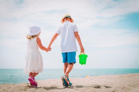 little boy and girl walk on summer beach, vacation concept