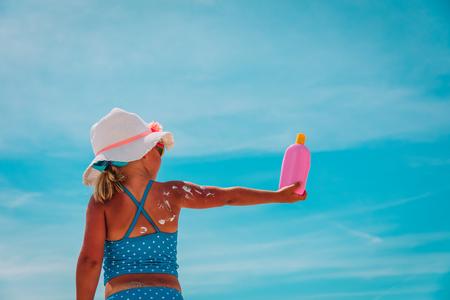 sun protection at beach- little girl applying sunblock cream on shoulder
