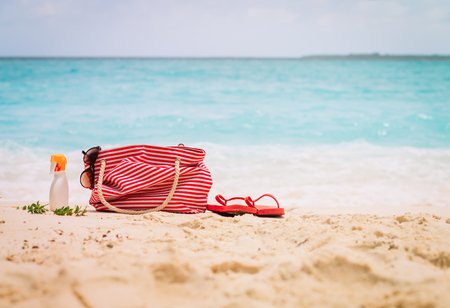 Beach bag, flip-flop and suncream on tropical beach 写真素材 - 105078173