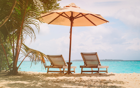 Beach chairs on the tropical beach, vacation concept Banco de Imagens