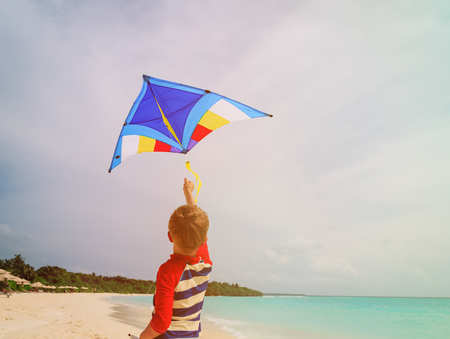 Little boy flying a kite on tropical beach Stock Photo