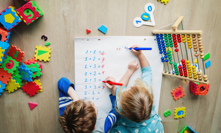 little boy and girl learn to write and calculate numbers