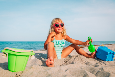 happy little girl play with sand on beach