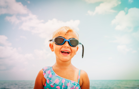 cute little girl with swimming googles at beach