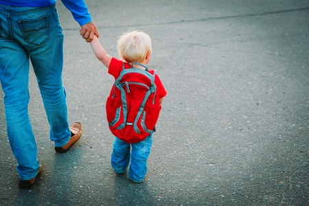 father walking little daughter to daycare, back to school