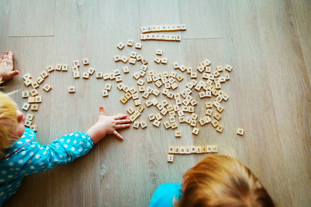 little girls play with letter puzzle in school or daycare Stock Photo