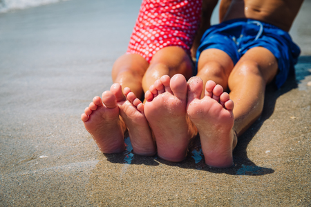 feet of boy and girl play with sand on beach Banque d'images
