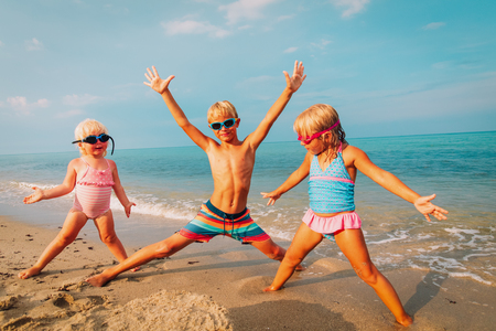 happy kids- little girls and boy-play enjoy beach